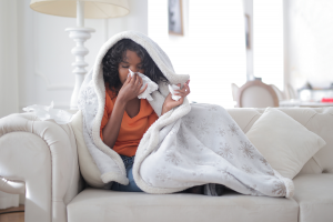 Woman on couch underneath blanket sneezing into a tissue.