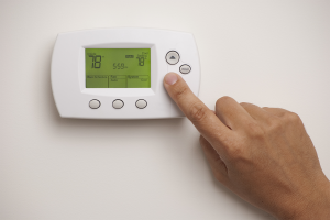 Person setting their white thermostat to save them money on their air conditioning bill.